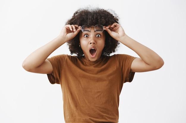 Retrato de mulher morena bonita, chocada e espantada, chocada e espantada, com penteado afro, tirando os óculos e segurando os óculos na testa, deixando o queixo cair de empolgação e emoção