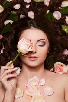Retrato de mulher morena bonita com cabelo longo cacheado e maquiagem brilhante witjh flores no cabelo