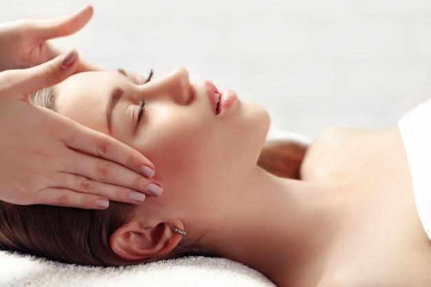 Retrato de mulher morena bonita e fresca, tendo massagem na cabeça