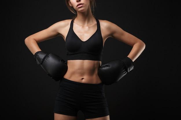 Retrato de mulher morena caucasiana em roupas esportivas, posando para a câmera com luvas de boxe durante treino no ginásio isolado sobre fundo preto