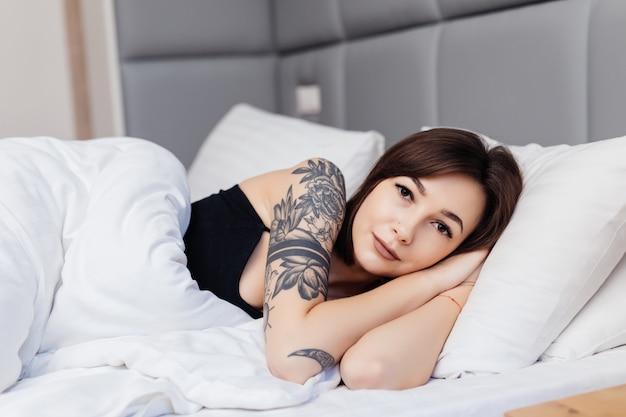 Retrato de mulher morena deitar na cama de manhã acorda esticando os braços e o corpo