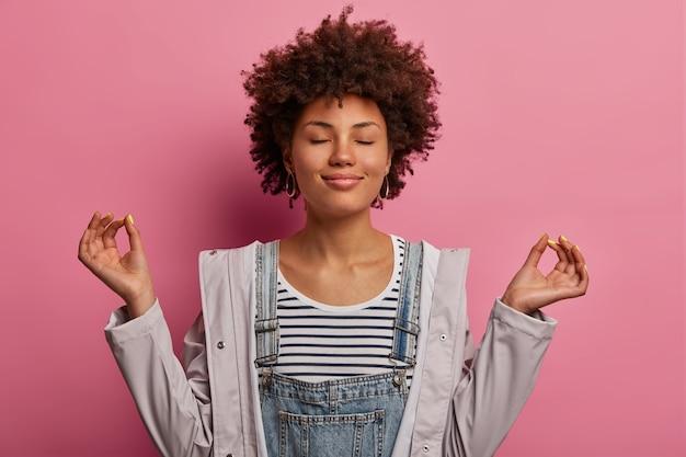 Retrato de mulher morena determinada e aliviada que medita com os olhos fechados, pratica exercícios de respiração ou ioga para se acalmar, fica em posição de lótus, posa sobre uma parede rosa, faz gesto zen