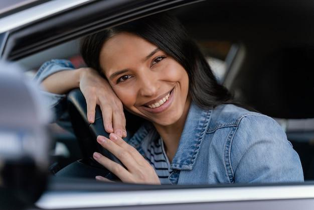 Retrato de mulher morena em seu carro