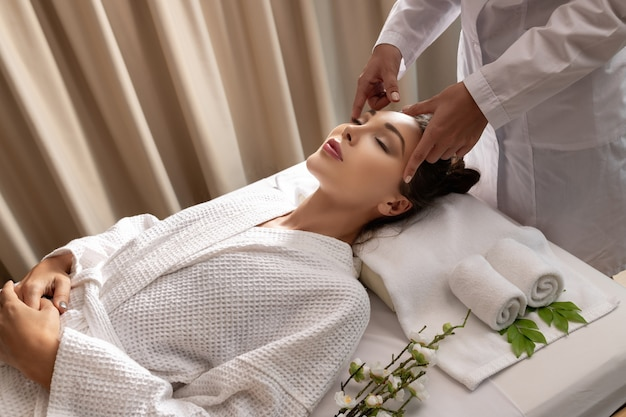 Retrato de mulher morena fresca e linda tomando a cabeça, em salão de spa de bem-estar,