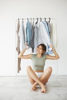 Retrato de mulher morena jovem alegre sorrindo sentado no chão entre as roupas no guarda-roupa do gancho sobre parede branca.