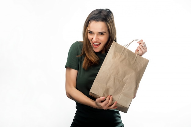 Retrato de mulher morena sorridente com sacola de compras nas mãos dela. jovem garota feliz, segurando o saco de compras de papel isolado