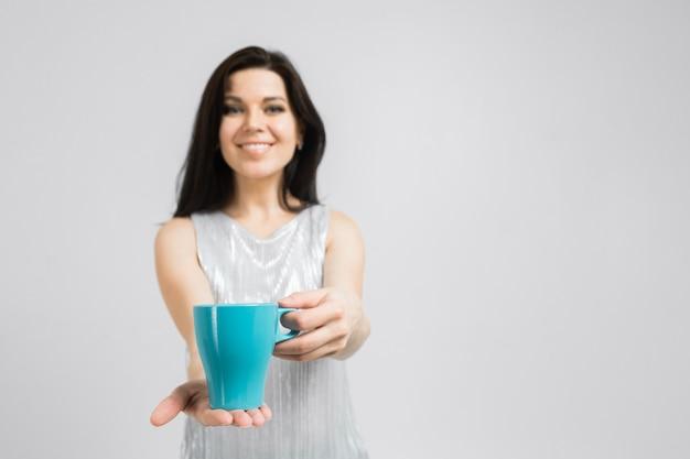 Retrato de mulher morena sorridente na blusa segurando uma xícara