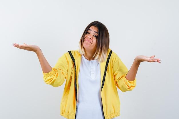Retrato de mulher mostrando gesto de desamparo em camiseta, jaqueta e olhar confuso