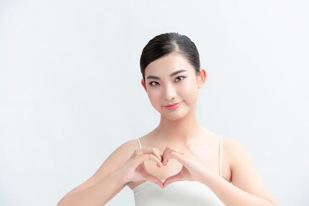Retrato de mulher mostrando sinal de figura de coração com as mãos perto do peito isolado