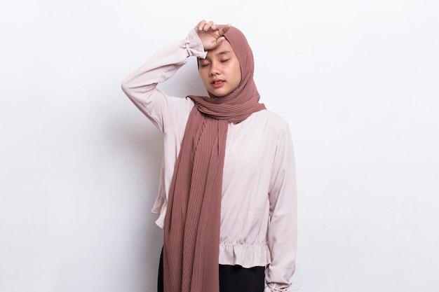 Retrato de mulher muçulmana asiática doente e estressada com dor de cabeça em fundo branco