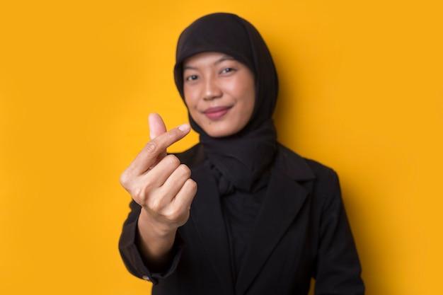 Retrato de mulher muçulmana asiática mostrando sinal de coração com os dedos
