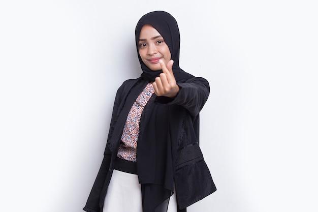 Retrato de mulher muçulmana asiática usando hijab mostrando sinal de amor de coração isolado no fundo branco