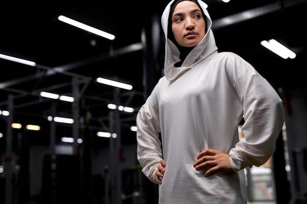 Retrato de mulher muçulmana esportiva séria posando para a câmera olhando para o lado no ginásio. em hijab branco. conceito de esporte