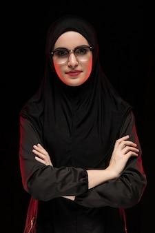 Retrato de mulher muçulmana jovem bonita na moda vestindo preto hijab e óculos moda conceito posando