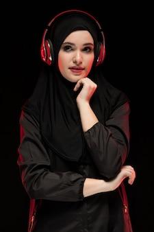 Retrato de mulher muçulmana usando hijab preto, ouvindo música em fones de ouvido