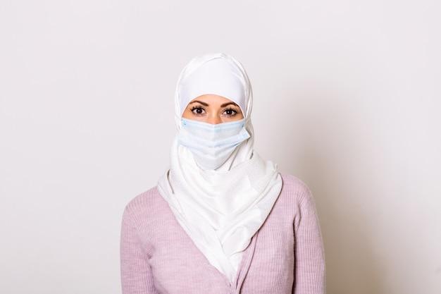 Retrato de mulher muçulmana usando máscara protetora para evitar coronavírus e anti-poluição atmosférica.