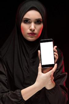 Retrato de mulher muçulmana usando preto hijab publicidade celular nas mãos dela