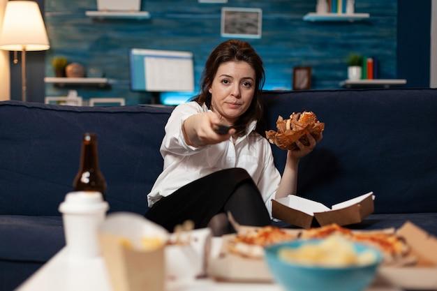 Retrato de mulher mudando de canal usando o controle remoto assistindo a uma série de filmes de entretenimento
