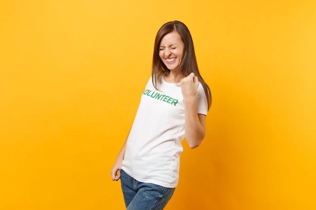 Retrato de mulher muito animado feliz feliz em t-shirt branca com voluntário de título verde de inscrição escrita isolado em fundo amarelo. ajuda de assistência gratuita voluntária, conceito de trabalho de graça de caridade.