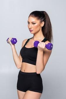 Retrato de mulher muito desportivo segurando pesos halteres isolados