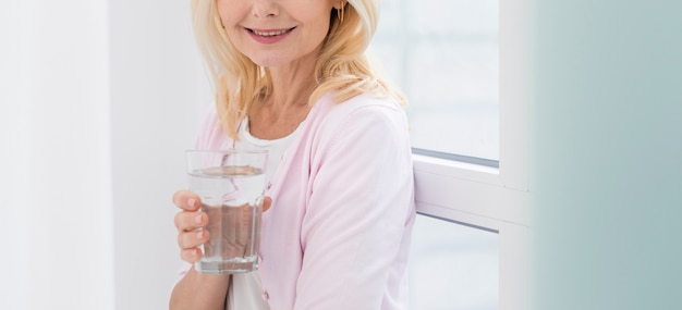 Retrato de mulher muito madura, segurando um copo de água