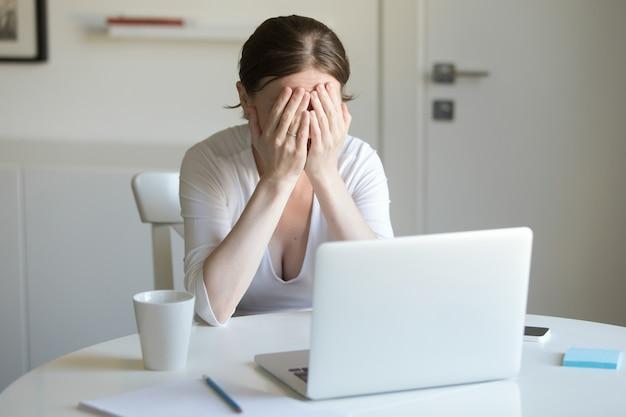 Retrato de mulher na mesa com laptop, mãos fechando rosto