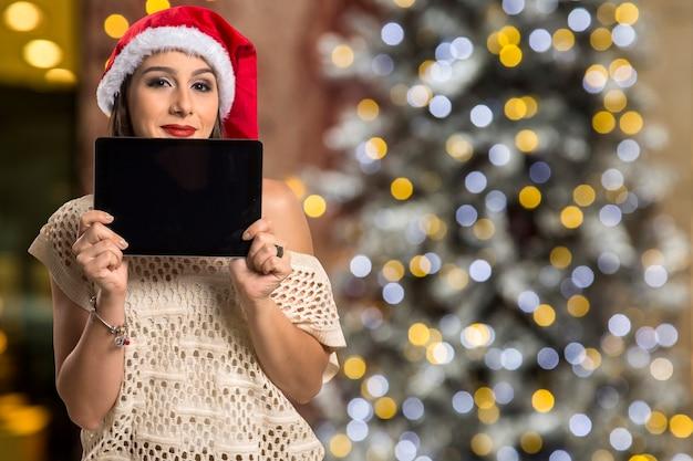 Retrato de mulher natal segurando o tablet. mulher sorridente e feliz com luzes de bokeh de natal