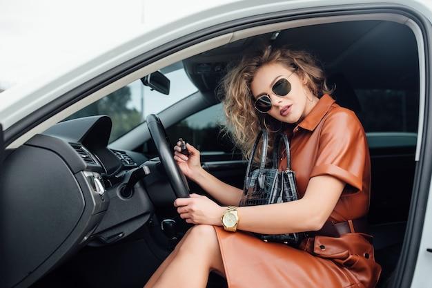 Retrato de mulher no carro no salão do carro com a chave na mão