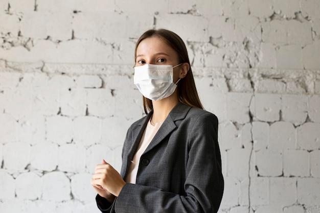 Retrato de mulher no escritório com máscara facial