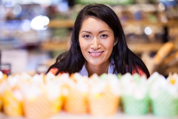 Retrato de mulher olhando cupcakes