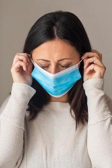 Retrato de mulher organizando máscara médica