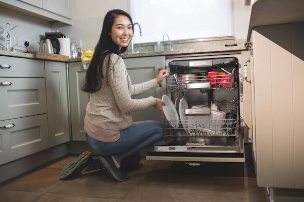 Retrato de mulher organizando pratos na máquina de lavar louça