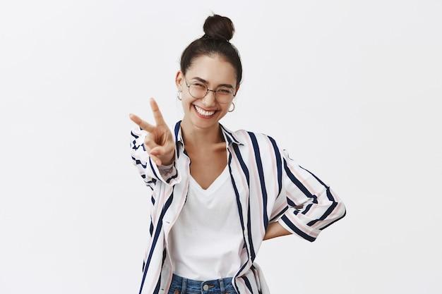 Retrato de mulher otimista, linda e alegre de óculos e camisa elegante, puxando a mão com o símbolo da paz, sorrindo amplamente de felicidade e diversão