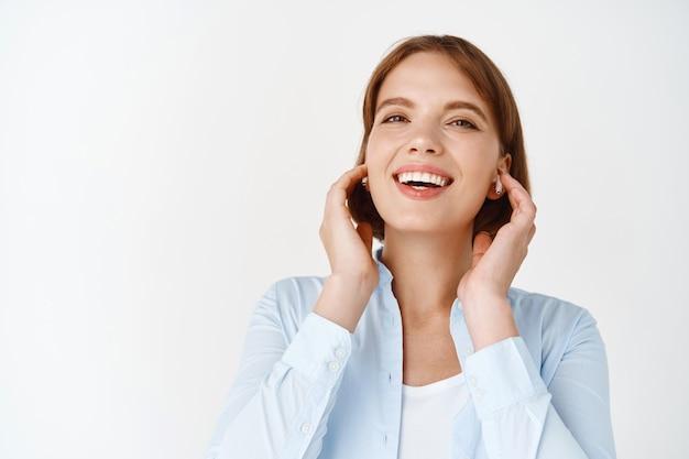 Retrato de mulher ouvindo música em fones de ouvido sem fio, sorrindo e tocando fones de ouvido nos ouvidos, feliz em pé na parede branca