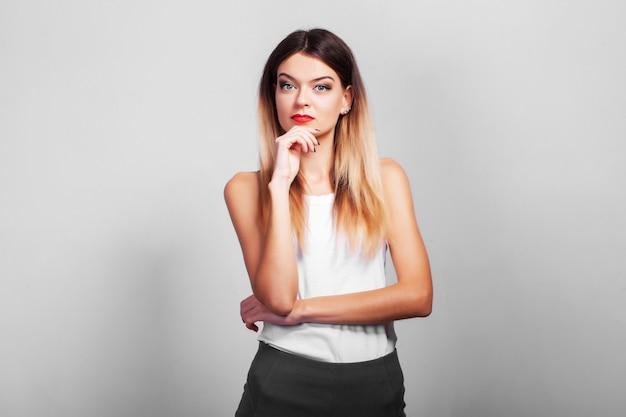 Retrato de mulher pensativa bastante confiante em cima de parede cinza com espaço de cópia
