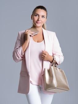 Retrato de mulher pensativa com carteira na mão e bolsa nas mãos sobre branco