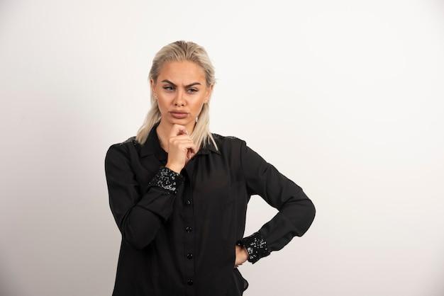 Retrato de mulher pensativa em camisa preta, posando em fundo branco. foto de alta qualidade