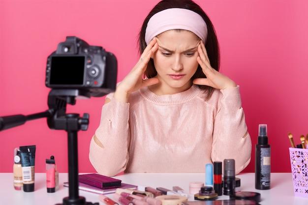 Retrato de mulher pensativa estressada usando bandana e blusa rosa