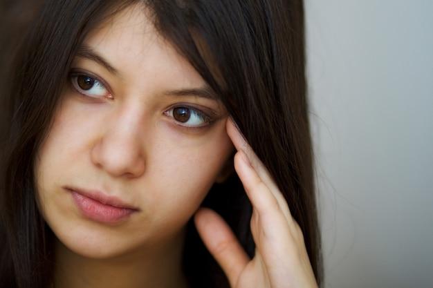 Retrato de mulher pensativa jovem bonita morena de olhos castanhos. copie o espaço