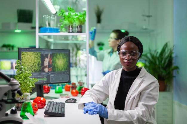 Retrato de mulher pesquisadora bióloga vestindo jaleco branco, olhando para a câmera