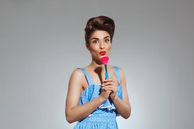 Retrato de mulher pin-up bonita no estúdio segurando o pincel de maquiagem