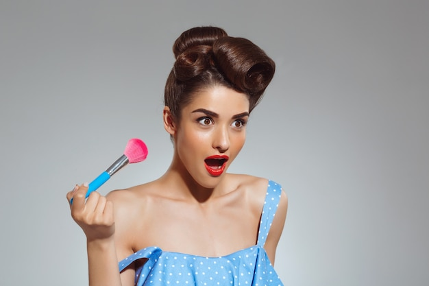 Retrato de mulher pin-up bonita segurando o pincel de maquiagem