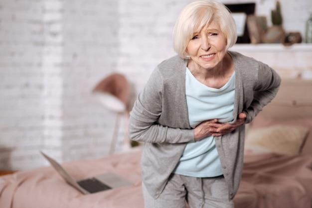 Retrato de mulher pobre sênior, inclinado para a frente por causa de forte dor abdominal.