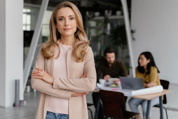 Retrato de mulher posando ao lado de seus colegas