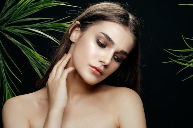 Retrato de mulher posando entre folhas de palmeira