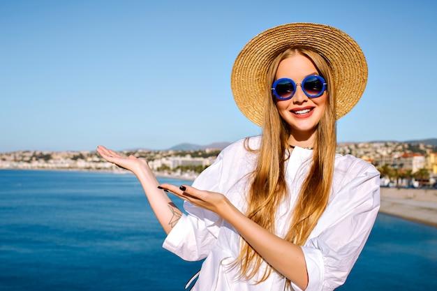 Retrato de mulher posando perto do mar azul na cidade francesa de cannes
