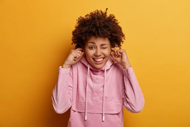 Retrato de mulher positiva de pele escura tapando os ouvidos com os dedos indicadores