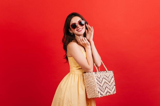 Retrato de mulher positiva em alto astral, posando na parede vermelha. senhora de cabelos escuros em roupa de verão brilhante, segurando uma bolsa de praia.
