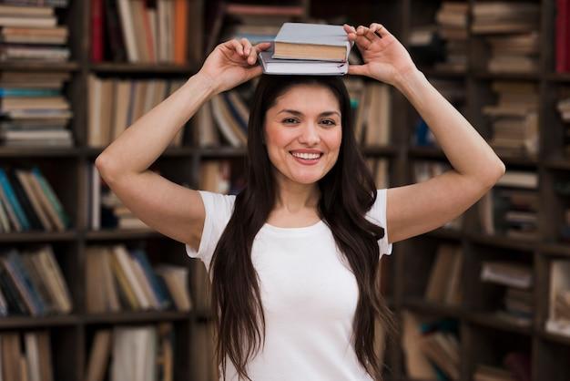 Retrato de mulher positiva sorrindo para a biblioteca