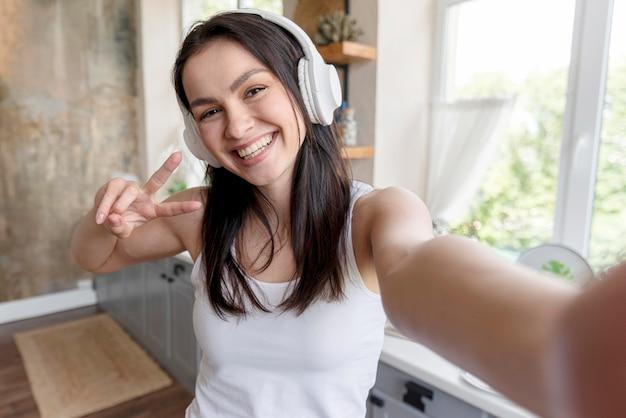 Retrato de mulher positiva tomando uma selfie
